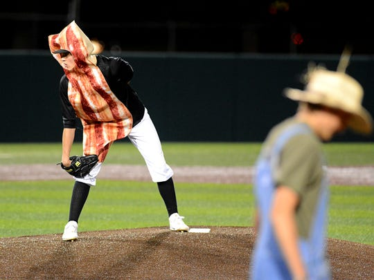 Abilene High's Bracken Hargrave, dressed as a strip of bacon, stares in for the sign during a costume scrimmage between the Abilene High and Cooper baseball teams Monday at Abilene Christian University's Crutcher Scott Field.
