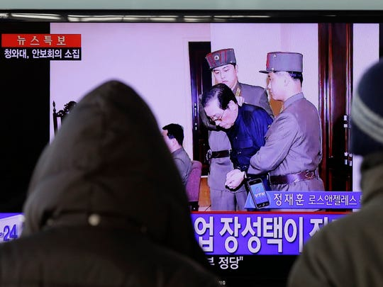 People watch a live TV news program showing that North Korean leader Kim Jong Un's uncle Jang Song Thaek, second from right, is escorted by military officers during a trial in Pyongyang, North Korea Thursday, Dec. 12, 2013, at the Seoul Railway Station in Seoul, South Korea.