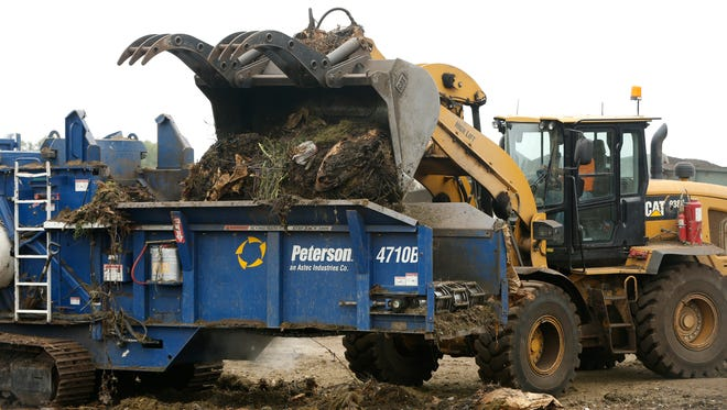 Paul Nemmers with Metro Waste Authority dumps yard waste into a horizontal grinder Wednesday, July 1, 2015 at the Metro Compost Center in Des Moines.