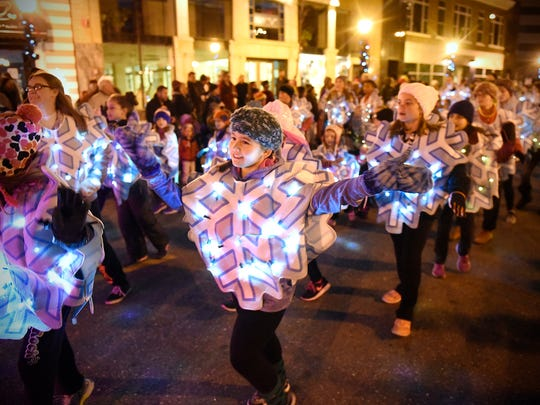 Dancers with Ms. Melinda's Dance Studio wave to the crowd Saturday during the 2015 Winter Nights and Lights parade in downtown St. Cloud.