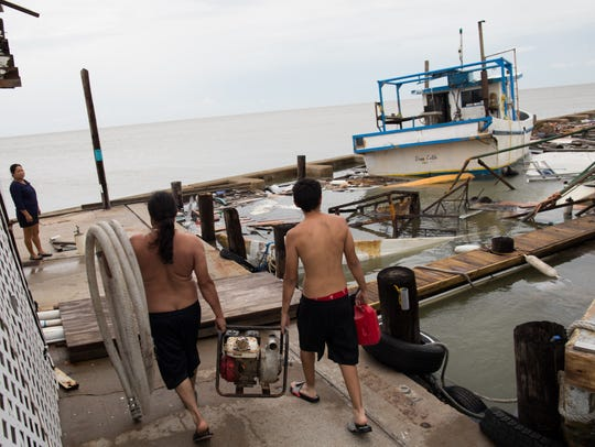 Sixto Ortiz and Juan Devora carry a water pump as they