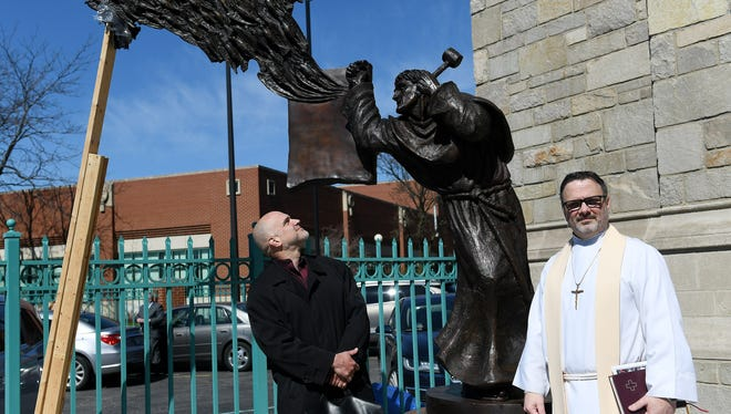 Artist Timothy Schmalz, left, looks up at the sculpture next to the Rev. D. Lee Andrzejewski after the dedication of the sculpture of Martin Luther and the 95 Theses by Timothy Schmalz at Historic Trinity Lutheran Church in Detroit on Sunday. The braces at the left will be removed after a couple days and the epoxy on the base is fully cured.