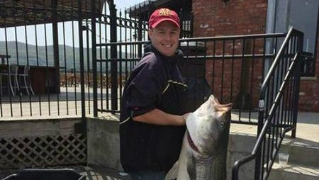 Eric Lester holds his 60-pound, state-record striped bass he caught on May 14 from the Hudson River in Orange County.