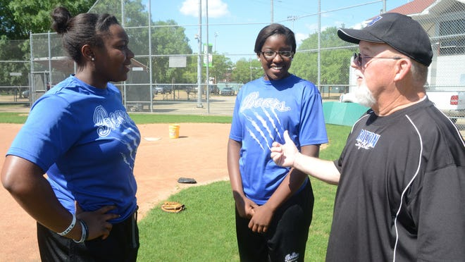 Bolton senior first baseman Whitney Jacobs (left), junior pitcher Destiny Williams and coach Ron Vidrine visit during practice Wednesday to prepare for the team's trip to the LHSAA FastPitch 56 state softball tournament in Sulphur.