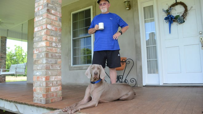 Bolton's Ron Vidrine is the All-Cenla Coach of the Year after guiding the Lady Bears to the Fast Pitch 56. He stands on his porch with his dog Gus.