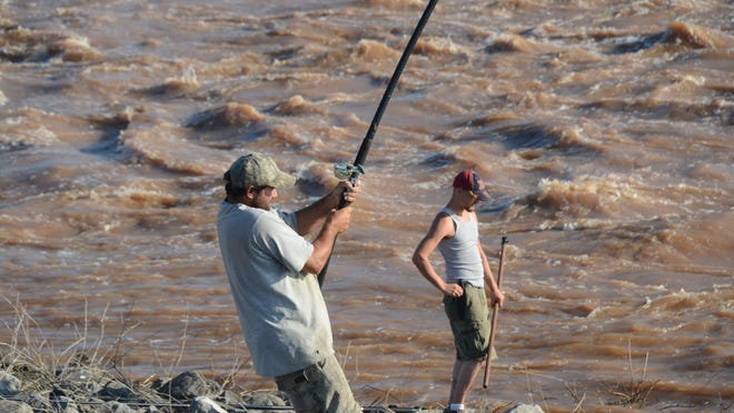 Benny Myers (left) reels in a catfish as Ryan McGlothin waits by the river's edge to pull it in during the Red River All-American Fishing Derby held Saturday at the John H. Overton Lock & Dam in Poland. The derby celebrated National Fishing and Boating week and the Louisiana free fishing weekend.