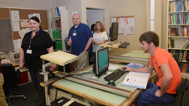 Tyler Stephens (right), a drafting student at Central Louisiana Technical Community College in Alexandria, studies while teachers from various junior high and high schools take a tour of the classroom and campus Tuesday.