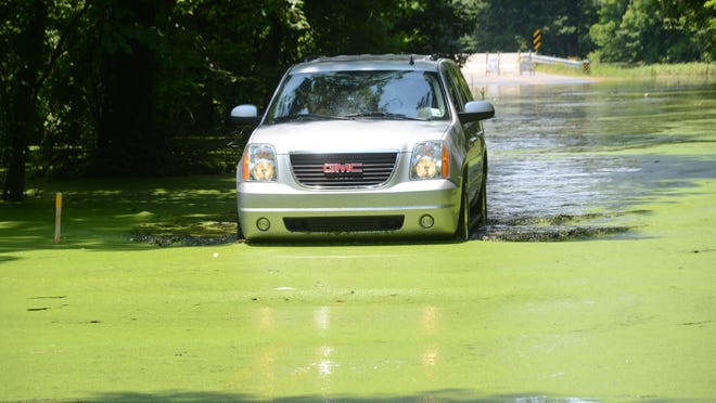 A sport-utility vehicle slowly crosses the water covering Rigolette Road Wednesday.
