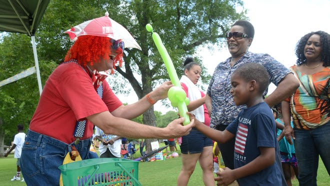 Curly the Clown presents Aaron Brevelle, 7, with a balloon sword at the Children's Fun in the Park at Frank O. Hunter Park which was part of the Juneteenth celebrations held Saturday. Aaron was with his grandmother Chandrika Hall.