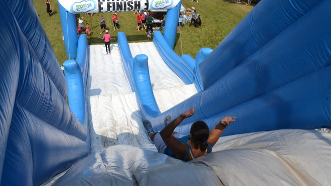 """A runner slides down the finish line of the """"Insane Inflatable 5K"""" at the former Red Cedar Golf Course in Lansing in 2014."""