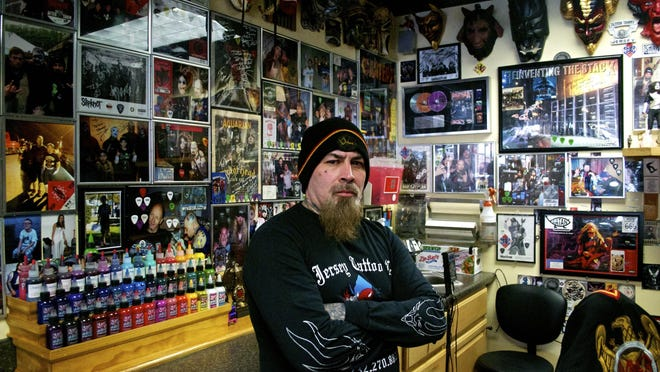 Tattoo Tommy standing in front of his memorabilia from over the years.