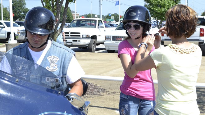 Linda Doty, right, helps fasten her daughter Taylor Doty's helmet as her ride, an anonymous officer who worked with her father, waits at the Poker Run on Saturday.