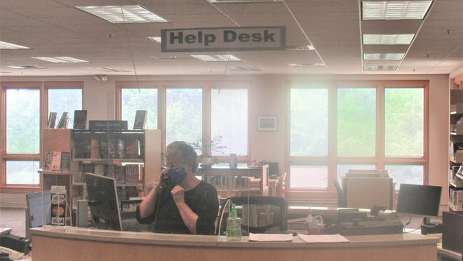 Marilyn Gingerich fields a phone call behind the new plexiglass dividers at the help desk of the central branch of the Holmes County District Public Library, which will reopen Monday, June 15, by appointment only.