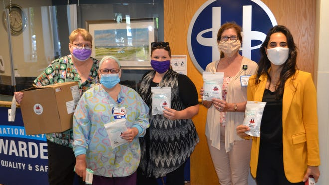 From left to right, registered nurses Kathleen McCormack  and Wendy Baron and Lisa Pedranti and Cathy Mallinson of Signature Healthcare received a donation of 250 KN95 facemasks last week from Nora Yousif (on the far right), a financial adivsor from Empower Wealth Group in Easton. Yousif is also a student in MIT's executive MBA program and part of a campaign called Masks 2 Heroes that has donated masks to frontline workers and provided cloth masks to the public.