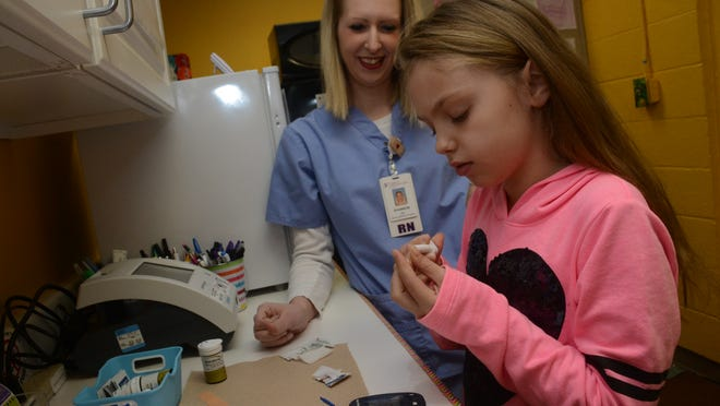 Lilly Peevy, a diabetic student at Lessie Moore Elementary School in Pineville, checks her blood sugar level under the supervision of Shannon Segura, an RN with the Christus Cabrini School-Based Health Center at the school, on Friday.