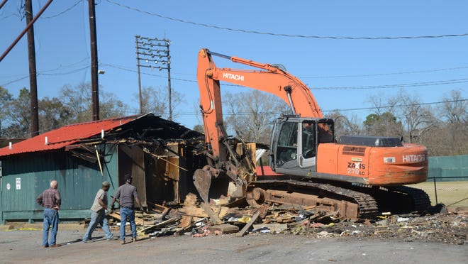 Workers on Wednesday demolish portable buildings that were destroyed by a Dec. 20 fire at Bringhurst Field.