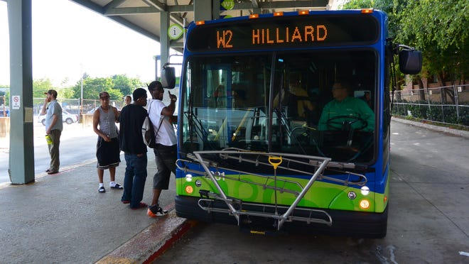Riders board a bus at Asheville Redefines Transit's downtown transfer station.