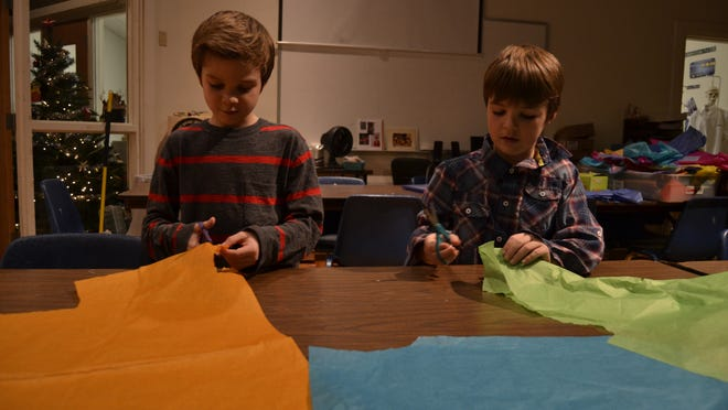 Cole Pangborn, 7, and Luke Pangborn, 9, cut pieces of tissue paper as part of the holiday crafts at Roberson Museum and Science Center on Sunday.