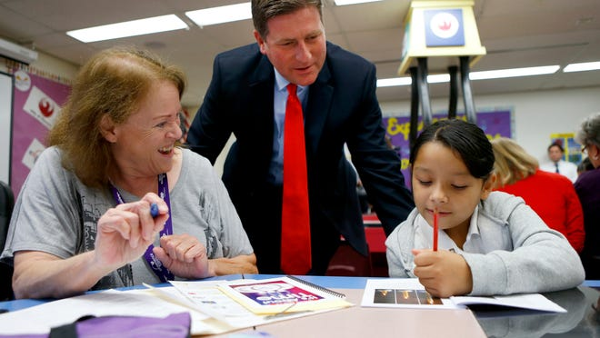 AARP volunteer Kathryn Smith and Phoenix Mayor Greg Stanton look on as Jazmin Quintero, 7, a second-grader at Wilson Primary School in Phoenix, shows off her reading skills. An AARP program helps first-, second-, and third-graders get up to speed in reading.