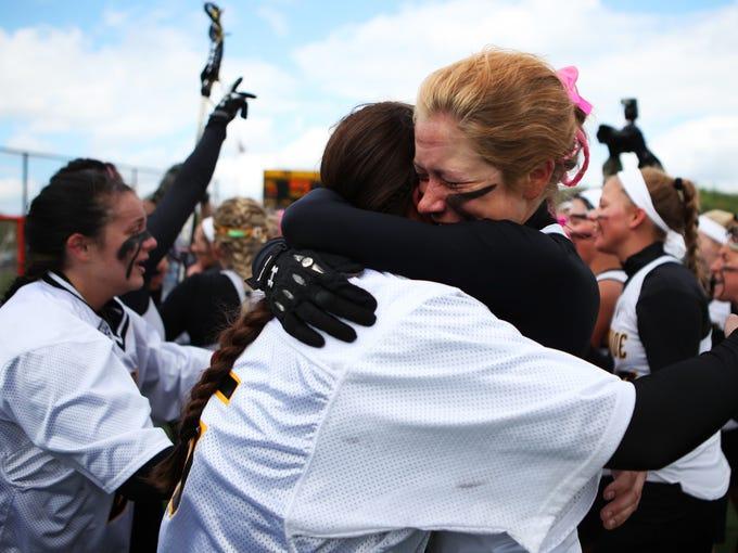Elizabeth Lacomb embraces a teammate Sunday after MCC won the NJCAA national title Sunday.