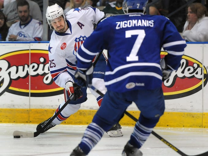 Rochester's Mark Mancari, left, fires the puck past Toronto's Mike Zigomanis during game 3 of the Western Conference quarterfinals of the 2013 Calder Cup Playoffs held at the Blue Cross Arena at the Rochester Community War Memorial on Wednesday, May 1, 2013. With the 3-2 overtime win, theToronto Marlies swept the best-of-five series ending the Amerks season.