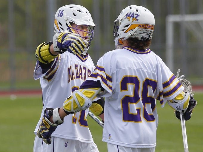 Nazareth's Collin Clark, left, and Troy Haefele celebrate a goal after the two combined for 9 goals as the Golden Flyers routed Castleton 25-4 during NCAA men's lacrosse playoff game Wednesday.