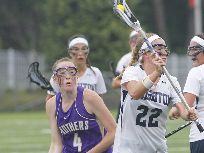 Brighton's Carly Randall, right, looks to get a shot on goal after getting by CBA's Hailey Dobbins during the Class B girls lacrosse championship in Cortland on June 8.