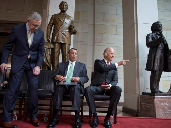 From left, Senate Majority Leader Harry Reid of Nevada, House Speaker John Boehner of Ohio and Vice President Joe Biden take their seats as as they arrive for a ceremony to dedicate the statue of Frederick Douglass, far right, Wednesday in the Emancipation Hall of the United States Visitor Center on Capitol Hill in Washington. The bronze statue of Douglass is by Maryland artist Steve Weitzman.