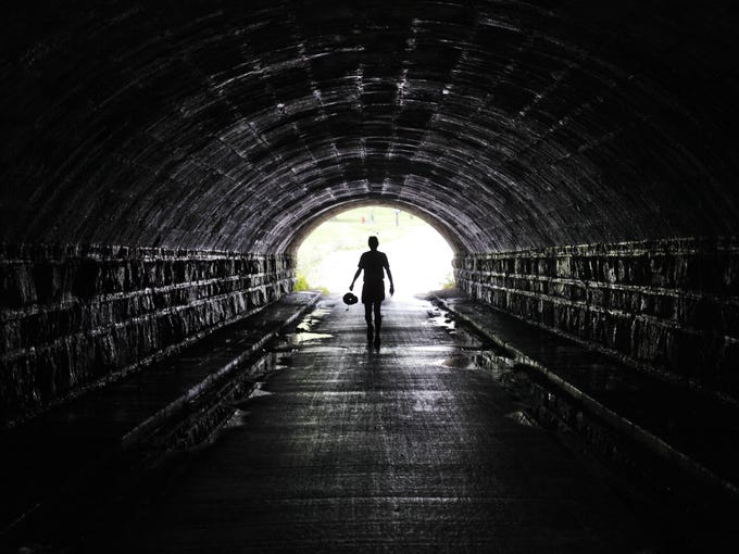 A cyclist on the Cycling the Erie Canal bike tour is silhouetted as he walks through the culvert under the Erie Canal in Medina.  The original culvert was built in 1823. Culvert Rd is the only road that goes under the Erie Canal.