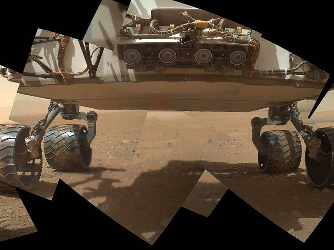 A view of the lower front and undercarriage of the Curiosity rover.