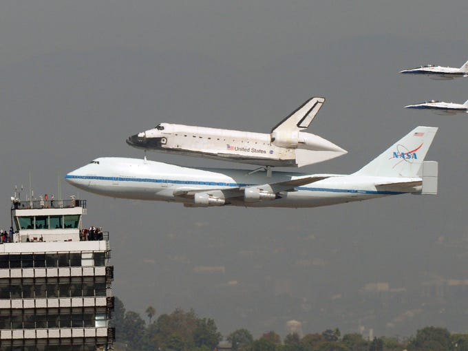 Space shuttle Endeavour riding atop a modified Boeing 747 passes onlookers in a control tower at the  Los Angeles International Airport, Friday.