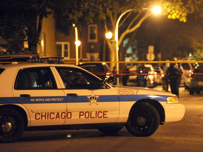 Chicago police investigate a shooting involving an officer in the North Austin neighborhood on Sept. 9. Driven by gangs, drugs and guns, the bloodshed in President Obama's adopted hometown has resulted in a body count of 400 through September.