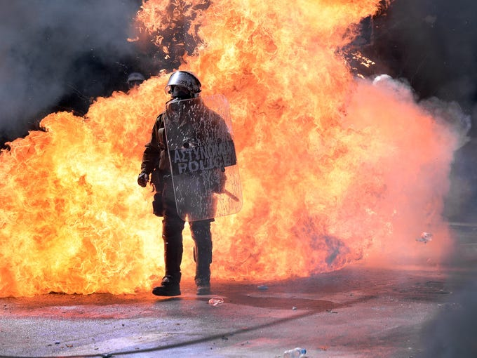 A firebomb explodes behind a Greek riot police officer during a battle with demonstrators in Athens. Thousands of people angry at a new round of government austerity measures staged a 24-hour general strike.