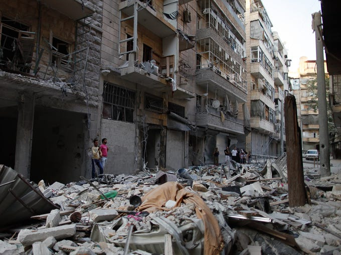 Residents survey damage caused by a Sept. 11 aerial bombardment on Mawsalet Street in Tariq al-Bab, a neighborhood of Aleppo, Syria.