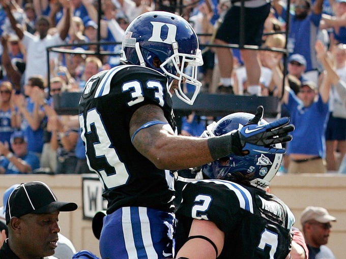 Duke Blue Devils wide receiver Desmond Scott (33) celebrates with wide receiver Conner Vernon (2) after Vernon scored a touchdown against the Virginia Cavaliers during the first half at Wallace Wade Stadium.