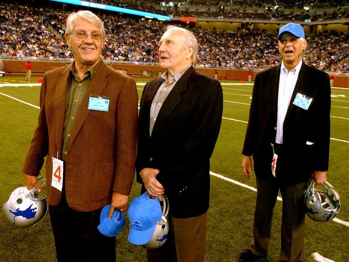 Lions greats Alex Karras and Joe Schmidt talk as Paper Lion author George Plimpton looks on during halftime ceremonies of a Lions game vs. the Vikings in 2003.