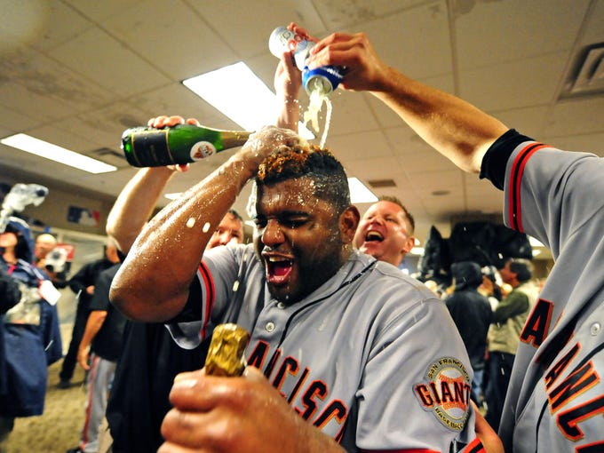 Game 5: Giants teammates give Pablo Sandoval a champagne shower in the locker room after defeating the Reds to win the NLDS.