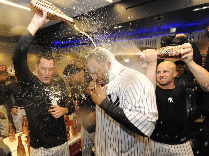 Game 5: Yankees players give starter CC Sabathia a champagne shower in the locker room following New York's 3-1 win over the Baltimore Orioles that clinched a berth in the ALCS.