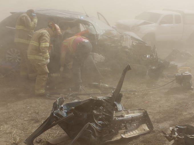 Tonkawa Fire Department rescue personnel work in a dust storm to remove a woman pinned in her vehicle after an accident on Interstate 35 on Oct. 18 near Kay County, Okla. Nine people were injured as amassive dust storm triggered multi-vehicle accidents as police to shut down the interstate amid near blackout conditions.