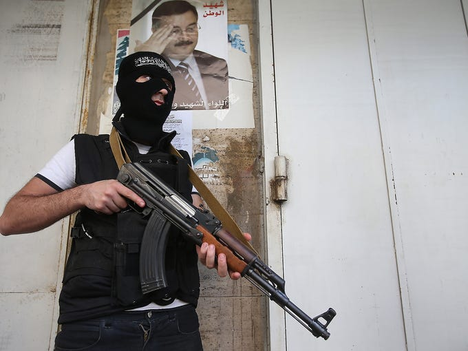 A masked Sunni gunman stands guard under a portrait of Lebanese Brig. Gen. Wissam al-Hassan on a blocked street leading to a Shiite neighborhood Oct. 22 in Beirut. The Lebanese army was deployed on a security operation to restore peace after fighting, triggered by the killing of the general Oct. 19, erupted between Sunni and Shiite gunmen.