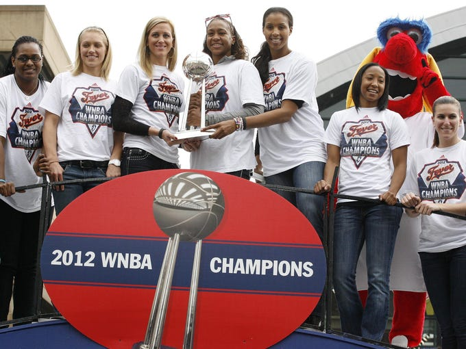 Fever players, from left, Sasha Goodlett, Erin Phillips, Katie Douglas, Tamika Catchings, Tammy Sutton-Brown, Briann January and Jeanette Pohlen pose with the WNBA championship trophy on a float in downtown Indianapolis.