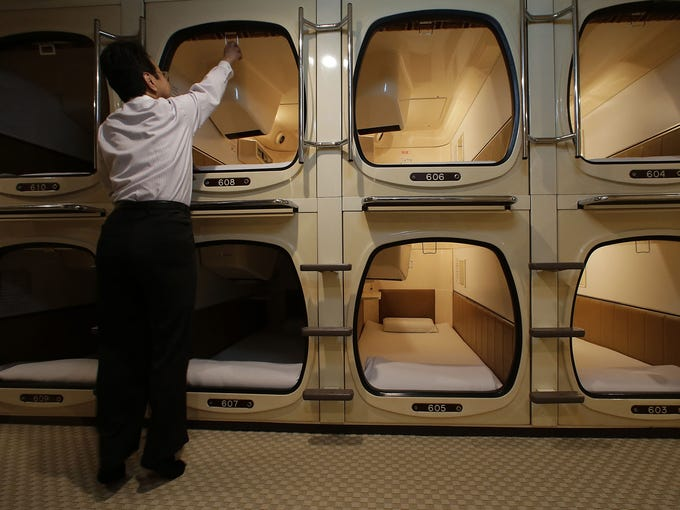 Akiyoshi Kaneko, manager of the Capsule & Sauna Century Shibuya hotel, prepares a capsule room on Oct. 29 in Tokyo. The capsule hotel concept has been around for at least 30 years, starting out as lodging for businessmen who needed a cheap place to stay after working or partying late and missing the last commuter train home.