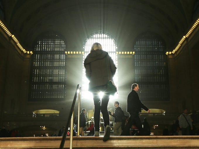 People walk through Grand Central Terminal as the sun rises during morning rush hour on Nov. 1 in New York City.