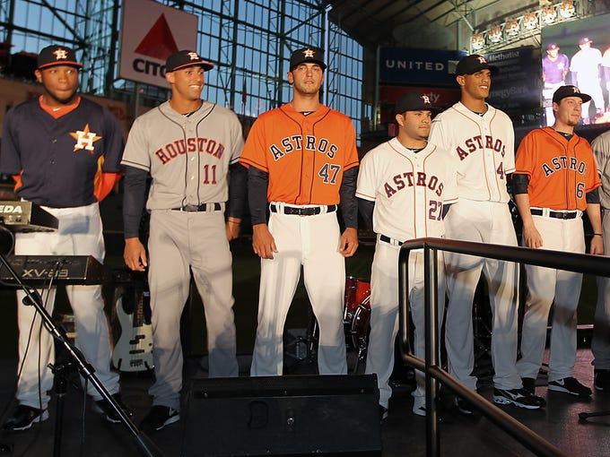 Houston Astros players and minor leaguers model the teams' new uniforms onstage at Minute Maid Park on Friday.
