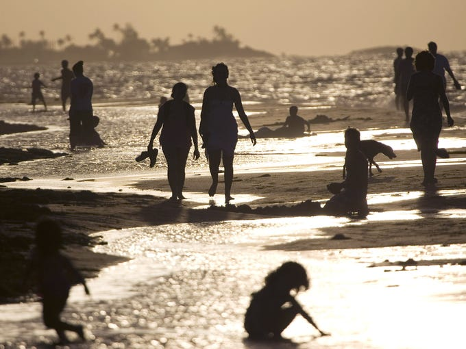 People walk and play on a beach in San Juan, Puerto Rico.