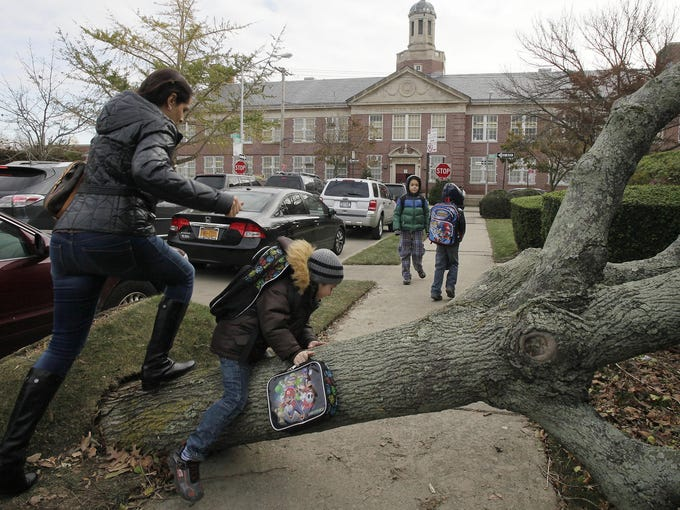 A woman and her son scramble over a toppled tree as they head to Public School 195 on Nov. 5 in the Manhattan Beach neighborhood in Brooklyn, N.Y. Students returned to school for the first time since Hurricane Sandy struck the city last week.