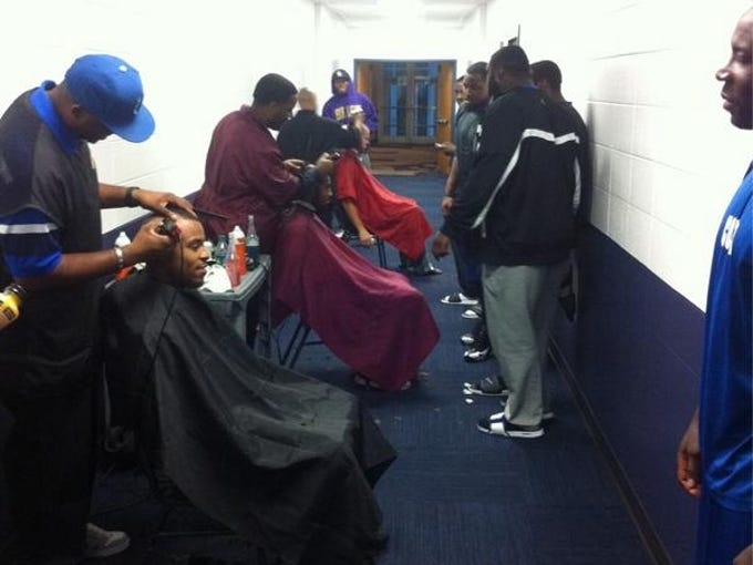 Colts players get their heads shaved by barbers in the hallway of their practice facility.