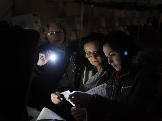 Poll workers Carole Sevchuk, left, Roxanne Blancero and Eva Prenga try to start an optical scanner on a voting machine on Nov. 6 inside a tent serving as a polling station in Midland Beach, N.Y. The original polling site, a school, was damaged by Hurricane Sandy.