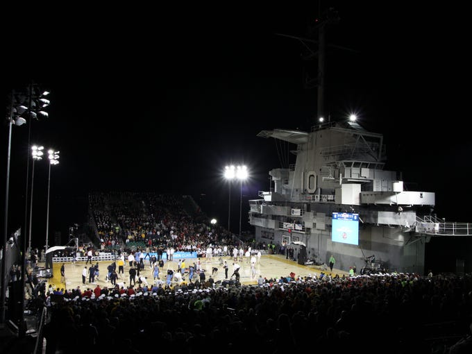 Coaches, players, and officials dry the court during the 2012 Carrier Classic between the Marquette Golden Eagles and the Ohio State Buckeyes on the USS Yorktown. The game was called off due to moisture on the floor.