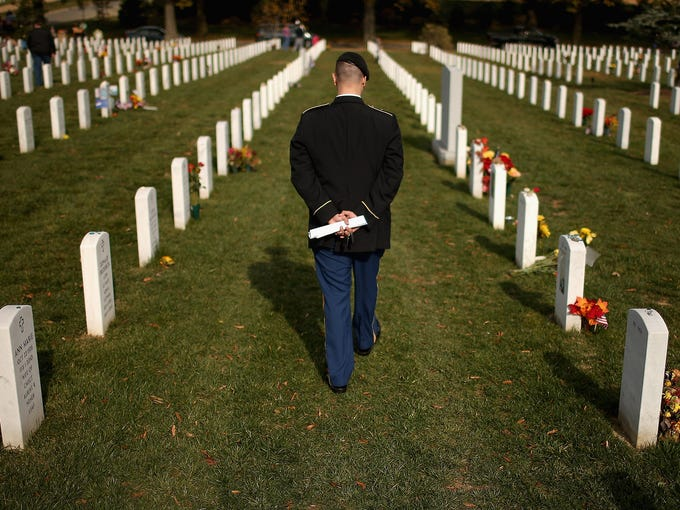 U.S. Army Staff Sgt. Luke Parrott walks between rows of headstones in Section 60 on Nov. 12 at Arlington National Cemetery in Arlington, Va. Several of Parrott's friends, and soldiers he served with, are buried here.